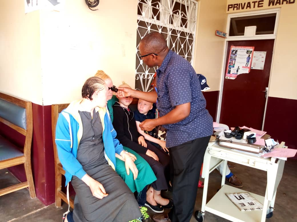 The Low Vision Therapist giving low vision devices to the albino after consultation